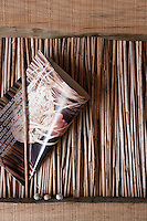 A woven tray on the rustic dining table in the cabin living room at CasasNaAreia contains a welcome leaflet