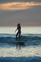 Pacific Beach, San Diego, California, USA:  Monday, January 19 2009.  A surfer rides her board in the surf at the bottom of Loring Street.  The Martin Luther King Jnr Day holiday was marked by warm weather, big surf and a technicolored sunset as much of the rest of the country shivered in the cold.