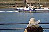 Dame mit großem Hut sitzt an der Rheinpromenade in Bingen am Rhein und schaut auf ein Schiff