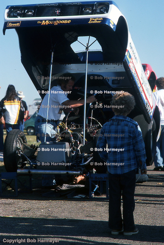 INDIANAPOLIS, INDIANA: A young fan watches a Funny Car team work on the engine during the 1976 NHRA US Nationals in Indianapols, Indiana.