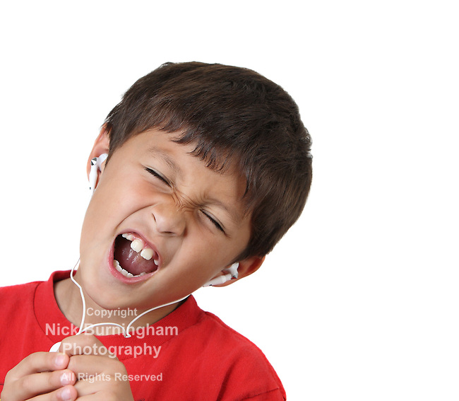 Young boy in red shirt singing with headphones on white background - with copy space to right