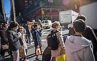 Visitors and workers in the Garment District in New York wait to cross the street on Friday, October 14, 2016.  (© Richard B. Levine)