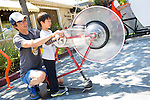 Guests power the string bike during a display in downtown Los Altos hosted by The Exploratorium museum.