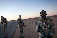 November 23, 2014 - Ubari region, Libya: Military men from the Third Force of Misrata armed forces stand guard at one of the check points of Al-Sharara oilfield installations powered off weeks ago in the Southwest of Libya. Fighting around Southwest Ubari region ignited after Tuareg militias from Mali and Libya sized control over the vast oilfield installations aligned with the Third Force of Misrata armed forces. Since then raged battles have taken place between two factions: one faction of Tuareg fighters lead by Third Force from Misrata pushing to clean the region from the other faction of Tebu tribal fighters defending their controlled territory. (Photo/Narciso Contreras)