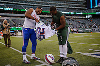 New York Jets, RB, Bilal Powell change T-shirts with Buffalo Bills, LB, Preston Brown, at the end of their NFL game at MetLife Stadium in New Jersey. 09.05.2014. VIEWpress