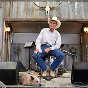 Cowboy Church. Texas, USA. 2007. Head pastor Ron Moore sitting on stage giving the Sunday service sermon, at his feet during the sermon is his faithful cattle dog Will. Between them they have written four albums of Christian Cowboy poetry, including songs like Cowboy Church, and resist the Devil and you won't have fleas.