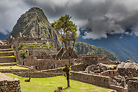 """Huayanapichu (young mountain) in the distance at Machu Picchu, the ancient """"lost city of the Incas"""",  built about 1400 CA. Discovered by Hiram Bingham in 1911. One of Peru's top tourist destinations."""