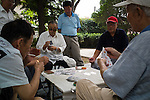 Men play cards in a park in the center of old Qingdao.