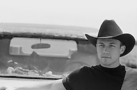 Young man in a black t-shirt and black cowboy hat, (b&w)