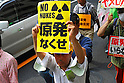 Tokyo, Japan - June 17: A man held a sign against nuclear power plants in Japan during a demonstration at Mitaka, Tokyo, Japan on June 17, 2012. As Japanese Government decided to restart Oi Nuclear Power Plants No.3 and 4 in Fukui, people spoke up against the restart throughout the nation. .