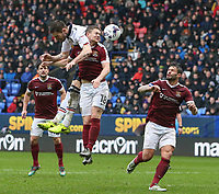Bolton Wanderers' Dorian Dervite competes for a header with Northampton Town's Aaron Phillips<br /> <br /> Photographer Alex Dodd/CameraSport<br /> <br /> The EFL Sky Bet League One - Bolton Wanderers v Northampton Town - Saturday 18th March 2017 - Macron Stadium - Bolton<br /> <br /> World Copyright &copy; 2017 CameraSport. All rights reserved. 43 Linden Ave. Countesthorpe. Leicester. England. LE8 5PG - Tel: +44 (0) 116 277 4147 - admin@camerasport.com - www.camerasport.com