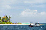 Huvadhoo Atoll, Maldives; the diving dhoni offshore of a remote, deserted island in the Indian Ocean, with palm trees and white sand beaches, surrounded by a shallow coral reef