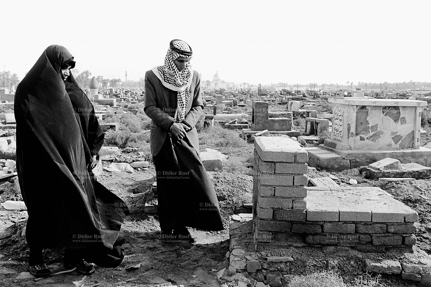 Iraq. Kufa cemetary. 15 km from Najaf. A couple (man and woman) pays respect on the tomb of a family relative. The woman wears the abaya and the hijab on her head to cover her hair. The Muslem Bin Akel mosque is in the background. The abaya, sometimes also called aba, is a simple, loose over-garment, essentially a robe-like dress, worn by some women in parts of the Islamic world. Traditional abaya are black and may be either a large square of fabric draped from the shoulders or head or a long caftan. The abaya covers the whole body except the face, feet, and hands. It can be worn with the niqab, a face veil covering all but the eyes. Some women choose to wear long black gloves, so their hands are covered as well. The word hijab (or hidjab) refers to both the veil covering the head and traditionally worn by muslim women (Islamic headscarf), but also the  modest muslim styles of dress in general. 27.02.04 © 2004 Didier Ruef ..