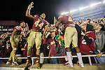 Florida State quarterback Deondre Francois, left, DeMarcus Walker, center, and Dalvin Cook celebrate with their fans after defeating Florida 31-13 in an NCAA college football game in Tallahassee, Fla., Saturday, Nov. 26, 2016. (AP Photo/Mark Wallheiser)