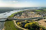 Nederland, Gelderland, Nijmegen, 24-10-2013; rivier de Waal met (de toerit naar ) de Waalbrug, gezien vanuit het Oosten, daarachter de spoorbrug met fietspad (De Snelbinder) en tenslotte de nieuwe stadsbrug van Nijmegen De Oversteek. Rechts van de rivier grondwerkzaamheden voor de dijkteruglegging Lent (Ruimte voor de Rivier). De dijken worden landinwaarts verplaats en er wordt een nevengeul gegraven. De huizen op de dijk blijven bestaan en komen te liggen op het Stadseiland Veur-Lent Nijmegen. In de verte de rookpluimen van de energiecentrale Electrabel Nederland.<br /> First bridge the Waal bridge on the river Waal, next the railway bridge with cycle path De Snelbinder (The Luggage strap) and finally the new city bridge of Nijmegen De Oversteek (The Crossing). Right of the river groundwork for the Dike relocation of Lent (project Ruimte voor de Rivier: Room for the River). <br /> luchtfoto (toeslag op standaard tarieven);<br /> aerial photo (additional fee required);<br /> copyright foto/photo Siebe Swart.
