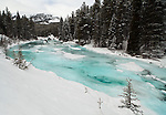 The turquoise waters of the Maligne River are partially frozen during winter in Jasper National Park, Alberta Canada.