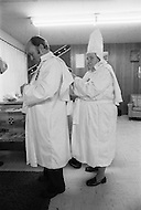 """Dunham Springs, Lousiana, December 1976: The members of Ku Klux Klan at a night ceremony which takes place ones a month; wearing white hoods and with the cross on fire. The local group cosists of 50 members; half of which are women. The leader of the cell is Bill Wilkinson who is also the leader of The National Movement, going by the title of """"Imerial Magician of the Invisible Empire of Horsemen of the KKK"""" The motto of the order is """"Be vigilant to Protect the white race."""" After the night ceremony, the members get together for dinner, preceded by a prayer."""