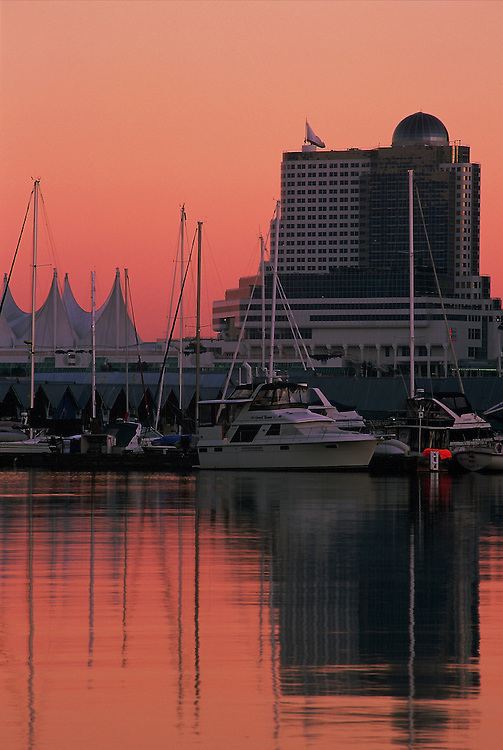 Sunset reflection of Canada Place and boats in marina, at Coal Harbor, taken from seawall in Stanley Park, Vancouver, BC.