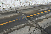 Crevice in asphalt road during spring thaw