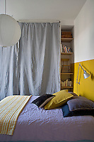 A section of the wall behind the bed has been painted a mustard yellow to resemble a headboard, its colour echoed in the combination of soft furnishings in the main bedroom