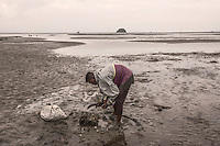 """Indonesia – Sumatra – Aceh - Lambaru Madjid – Kamaruzaman, 32-year-old fisherman is collecting mussels during the low tide where it used to be dry land before the tsunami submerged 200 meters of coastline under the ocean forever.  """"Villagers here have experience with big waves, but these were huge"""" he remembers, walking through the low-tide-mud to look for mussels. """"I realized it was a disaster when I saw the destroyed houses on the coastline""""."""