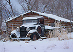Montana, Southwest, An old truck covered in snow in a rustic setting.