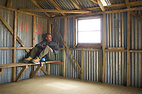 Single male sitting in mountain shelter