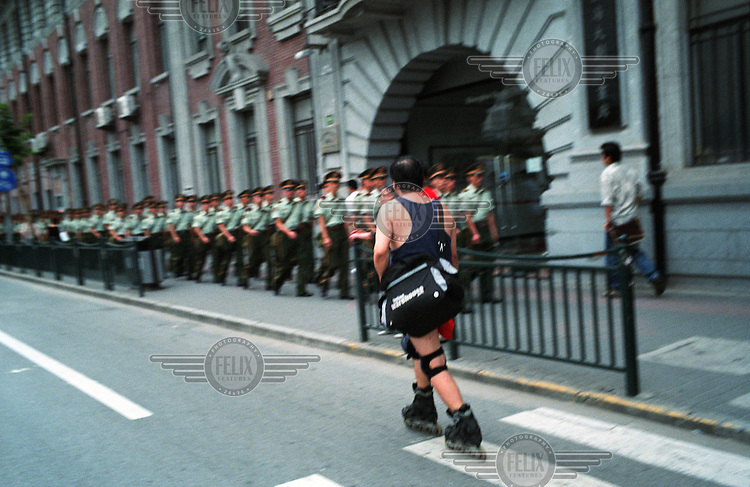 A man on rollerblades meets a group of paramilitary soldiers in Shanghai.