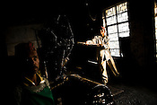 Indrey Sarki looks on as Rajkumar (right), a factory worker, shovels coal into a drier during the drying process at the Makaibari Tea estate, in Darjeeling, India.