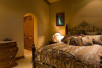Wrought iron bed is sen with beautiful bed linens and pillows
