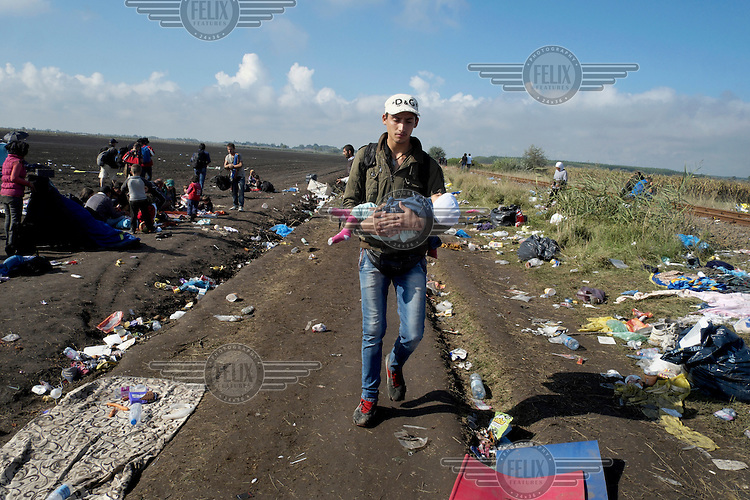 A Syrian refugee with his son in his arms walking from the Serbian border to a reception camp just inside the Hungarian border.<br /> <br /> Hungary, along with Italy and Greece, has seen a huge influx of refugees and migrants in 2015. Most of them cross the border into Hungary from neighbouring Serbia and usually intend to travel onwards to Austria, Germany or other northern European countries where they hope to claim asylum and find employment. Due to the large numbers of people entering the country illegally, Hungary has built a 175 km long, 4 metre high fence along its southern border with Serbia to try and keep them out. It has also announced that from Tuesday 15 September 2015 anyone crossing into Hungary illegally will be arrested and put in prison rather than being taken to a refugee camp.