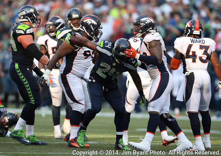 Seattle Seahawks running back Marshawn Lynch (24) dances between Denver Broncos safety Quinton Carter (38) and defensive tackle Sylvester Williams (92), after picking up a seven-yard gain against   in overtime at CenturyLink Field in Seattle, Washington on September 21, 2014.   Lynch ran for 88 yards and scored two touchdowns in the Seahawks 26-20 overtime win over the Broncos.  Providing blocking against the Broncos defenders is tackle Russell Okung (76)  and tight end Zach Miller (86)  ©2014. Jim Bryant Photo. All rights Reserved.