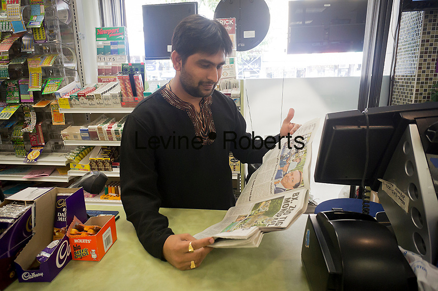 A newsstand operator in New York on Saturday, September 22, 2012 reads the NY Daily News. (© Richard B. Levine)