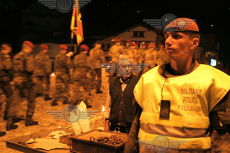 A man sells roasted chestnuts as members of the German NATO KFOR peacekeeping mission celebrate German National Unification Day in Prizren.