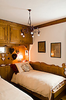A bespoke built in cupboard also works as a bedside table in this traditional mountain chalet