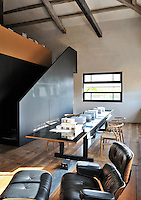 A functional, industrial space with exposed roof beams and a wood floor. An Eames recliner stands next to long black table and light wood chairs. A staircase with a side panel leads to an upper floor.
