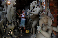 INDIA (West Bengal - Calcutta)  2008, An idol maker at work in his studio at Kumortuli. Kumortuli in North Calcutta is the hub of Durga idol makers. During the other time of the year the artists engage themselves in prepairing other idols and masks depending on the assignments. But the most of the earning they aquire from making Durga idols. A Durga idol can cost up to 7000 usd. Which is a big price in Indian Currency.  Durga Puja Festival is the biggest festival among bengalies.  As Calcutta is the capital of West Bengal and cultural hub of  the bengali community Durga puja is held with the maximum pomp and vigour. Ritualistic worship, food, drink, new clothes, visiting friends and relatives places and merryment is a part of it. In this festival the hindus worship a ten handed godess riding on a lion armed wth all possible deadly ancient weapons along with her 4 children (Ganesha - God for sucess, Saraswati - Goddess for arts and education, Laxmi - Goddess of wealth and prosperity, Kartikeya - The god of manly hood and beauty). Durga is symbolised as the women power in Indian Mythology.  In Calcutta people from all the religions enjoy these four days of festival in the moth of October. Now the religious festival has become the biggest cultural extravagenza of Calcutta the cultural capital of India. Artistry and craftsmanship can be seen in different sizes and shapes in form of the idol, the interior decor and as well as the pandals erected on the streets, roads and  parks.- Arindam Mukherjee