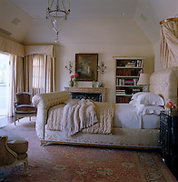 The luxurious master bedroom has a large, upholstered bedstead and silk curtains
