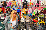 OCTOBER 22, 2011 - MERRICK, NY: Young woman looking at colorful animal knit hats on display at booth at Merrick Street Fair, New York, USA.