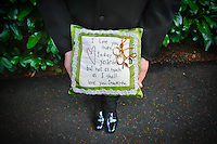 The son of the groom holds a hand-made pillow to transport the wedding rings of the couple to the ceremony. (Photo by Andy Rogers/Red Box Pictures)
