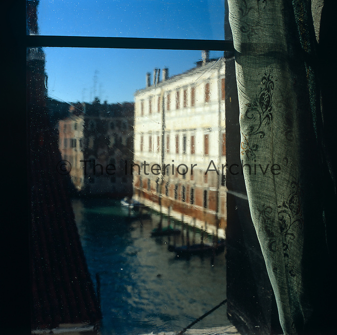 View over the canal and a row of gondolas through the thick 17th century glass of an original Renaissance window in the Venetian palazzo