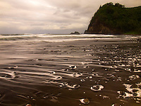 The ocean streaks back from the rocks scattered along the black sand shore of Pololu Valley Beach on the Big Island.