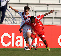 Luca Gasparotto (13) of Canada fights for the ball with Aldair Paredes (11) of Panama during the semifinals of the CONCACAF Men's Under 17 Championship at Catherine Hall Stadium in Montego Bay, Jamaica. Canada defeated Panama, 1-0.