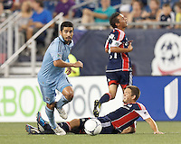 Sporting Kansas City midfielder Paulo Nagamura (6) controls the ball despite slide tackle attempt by New England Revolution substitute midfielder Kelyn Rowe (11). In a Major League Soccer (MLS) match, Sporting Kansas City defeated the New England Revolution, 1-0, at Gillette Stadium on August 4, 2012.