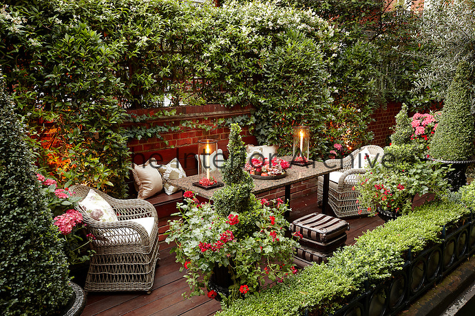 A secluded decked terrace area with outdoor seating and table.