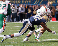 Pitt defensive back Phillipie Motley (32) tackles Miaimi wide receiver Braxton Berrios. The Miami Hurricanes football team defeated the Pitt Panthers 29-24 on  Friday, November 27, 2015 at Heinz Field, Pittsburgh, Pennsylvania.