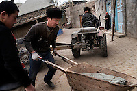 Uighur workers transport building materials used in home improvements in the Old City section of Kashgar, Xinjiang, China.