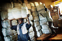 Men transporting bundles of long-lasting insecticide-treated bed nets that will be distributed by the NGO Malaria Consortium to people at risk around Masindi.