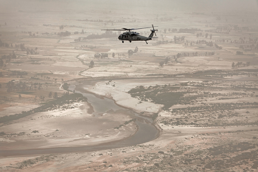 """A Blackhawk passes over Kandahar's Arghandab district. Scenes from the medical evacuations of wounded Americans, Canadians, and Afghan civilians and soldiers being flown by Charlie Co. 6th Battalion 101st Aviation Regiment of the 101st Airborne Division. Charlie Co. - which flies under the call-sign """"Shadow Dustoff"""" - flies into rush the wounded to medical care out of bases scattered across Oruzgan, Kandahar, and Helmand Provinces in the Afghan south. These images were taken of missions flown out of Camp Dwyer in Helmand Province."""
