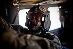 "10/6/2010 Helmand Province, Afghanistan.Flight medic SGT Tyrone Jordan, Charlie Co. 1-214th, preps the back of the Medevac UH-60 Blackhawk helicopter, hanging IV bags and getting other medical materials ready, enroute to a point of injury in Helmand Province, Afghanistan...The Helicopter Medevac teams of Task Force Destiny, based at Forward Operating Base Dwyer in Afghanistan's war-torn Helmand Province have a tough job. Servicing a large area that includes still restive southern Marjah, and much of the Helmand River Valley, TF Destiny answers the call to transport gravely wounded US Marines and Afghan civilians from the point of injury in the field to Role 3 trauma centers on bases in the area--often times landing under fire to extract Marines and soldiers that would otherwise succumb to their wounds. After the Medevac helicopter and it's ""chase"" UH-60 Blackhawk companion aircraft get a call, they can be on the ground picking up a patient in as little as 20 minutes--delivering the fallen to a surgical theater within what flight medics refer to as ""the golden hour""--or the hour after a catastrophic injury during which a patients transfer from basic battlefield triage care to a modern trauma surgical unit can mean the difference between life and death. ."